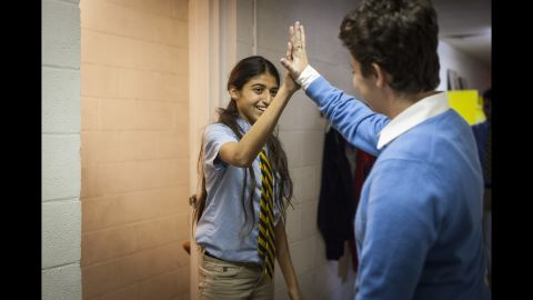 Mufleh high fives a Fugees Academy student. The school graduated its first class in the spring of 2016.