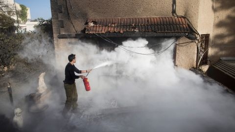 An Israeli soldier helps extinguish a fire next to a house on November 25 in Haifa, Israel.