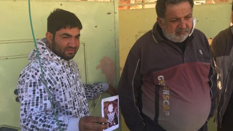 Distraught father Omar Ali holds a picture of his daughter Amira who was killed by an ISIS mortar.