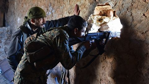 A pro-government soldier mans a damaged house in the recently recaptured village of Joubah in Aleppo province on Friday.