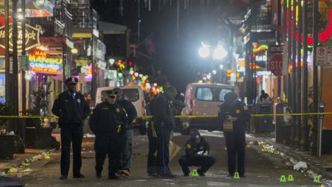 New Orleans Police Department investigators study a crime scene after a fatal shooting in New Orleans, Sunday, November. 27, 2016.