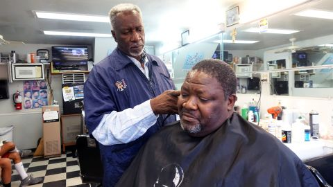 Charleston, South Carolina barbershop owner Thad Miller cuts the hair of customer Joseph Singleton. Both men are paying attention to the two overlapping racially-charged trials of Michael Slager and Dylann Roof