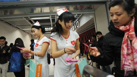 Volunteers hand out condoms in a subway station in Wuhan on World AIDS Day.