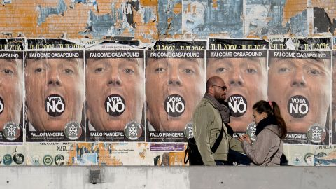 """People walk past posters for far-right political movement CasaPound, which is calling for a vote """"No"""" in Italy's constitutional referendum."""