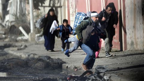 Iraqis run for cover as ISIS fighters clash with government forces last week in northeastern Mosul.