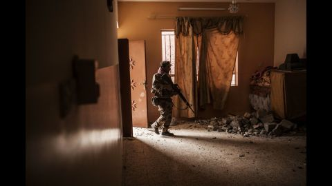 An Iraqi soldier searches a home for ISIS militants after Iraqi forces retook the village of Al-Qasr on Wednesday, November 30.