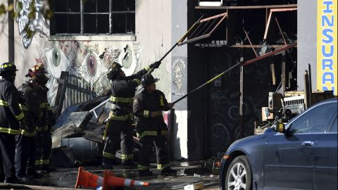 Firefighters clear an entry to the smoldering warehouse.