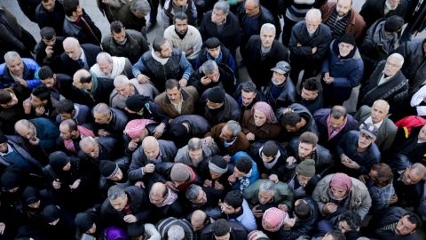 Syrian men wait for a security check to be able to return to their homes in Masaken Hanano in eastern Aleppo on Sunday.