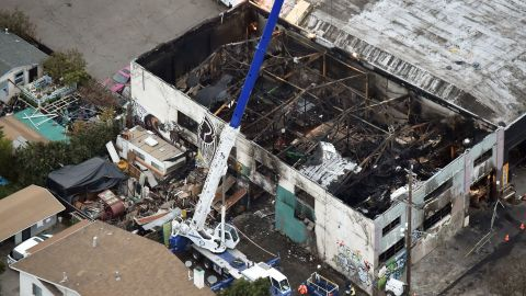 A crane is used to lift wreckage as part of search efforts in a fire-ravaged warehouse on December 05, 2016 in Oakland, California.  The death toll from a massive weekend fire at a warehouse near San Francisco shot up to 36, as authorities launched a criminal probe and pushed forth with recovery efforts.  / AFP / Josh Edelson        (Photo credit should read JOSH EDELSON/AFP/Getty Images)