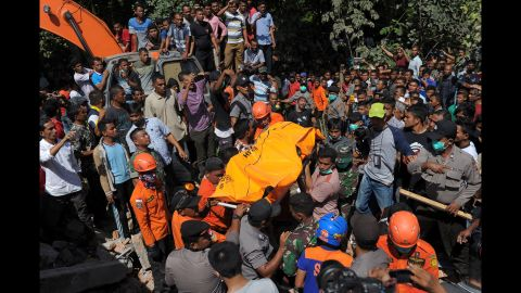 Rescuers carry the body of an earthquake victim in Pidie Jaya.