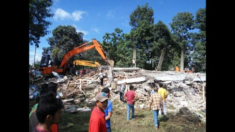 Rescuers use heavy machinery to search for potential survivors under the rubble of a collapsed building in Pidie Jaya.