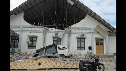 A man rides past a hospital that was heavily damaged by the  quake in Pidie Jaya.