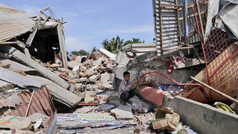 A boy takes shelter from the sun amid the rubble in Pidie Jaya.