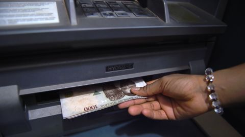 Nigerians are overwhelmingly positive about their country's future economic prospects with 86% believing the economic situation will leap forward in the next 12 months.<br /><br />Pictured here, a customer withdraws Nigerian naira from an automated teller machine  in Asaba, Delta State, in November 2016.
