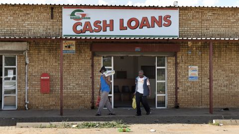 A broad majority of South Africans (62%) think the country's economic situation will improve in the next year. The study further found black South Africans to be significantly more optimistic than mixed-race and white South Africans.<br /><br />Pictured here, people walk in front of a Cash Loan shop in Marikana in April 2014.