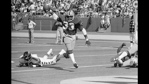 """Tony Dorsett of the University of Pittsburgh holds the ball aloft as he runs past Temple safety Chuck Gill during a game in Pittsburgh on September 27, 1976. After a career in professional football, Dorsett <a href=""""http://www.espn.com/dallas/nfl/story/_/id/12300070/tony-dorsett-battling-cte-had-no-idea-end-was-going-this"""" target=""""_blank"""" target=""""_blank"""">said</a> he now struggles with trauma-induced memory loss."""
