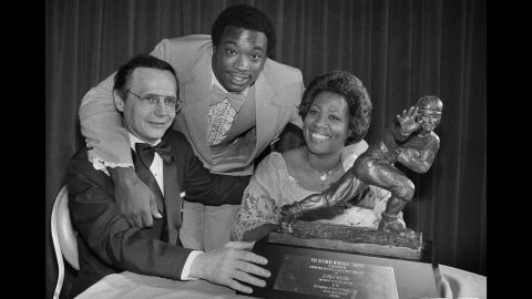 """Heisman Trophy winner George Rogers, center, poses with his mother, Grady Rogers, and South Carolina Gov. Richard Riley, after he was formally presented with the trophy at a dinner in New York on December 12, 1980. In accepting the trophy, Rogers paid tribute to his mother and his coaches. """"I'm happy for the University and for my teammates, too,"""" Rogers said."""