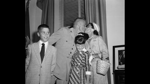 """Glenn and his wife, Annie, sandwich their daughter, Carolyn """"Lyn,"""" as they embrace following a ceremony honoring his feat. Son David is at left."""