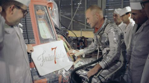 Glenn inspects artwork to be painted on the outside of his Mercury spacecraft, which he nicknamed Friendship 7. On February 20, 1962, Glenn  became the first American to orbit the Earth. After orbiting the Earth three times in four hours and 55 minutes, the Friendship 7 landed in the Atlantic Ocean.