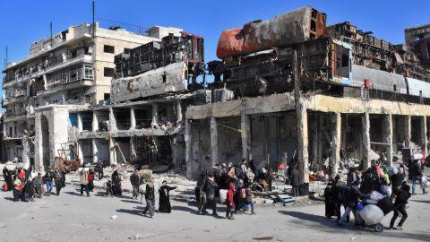 Residents of a newly retaken eastern neighbourhood of Aleppo pass a makeshift barricade Thursday.