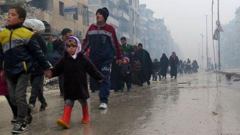 Syrian residents, fleeing violence in the restive Bustan al-Qasr neighbourhood, arrive in Aleppo's Fardos neighbourhood on December 13, 2016, after regime troops retook the area from rebel fighters.  Syrian rebels withdrew from six more neighbourhoods in their one-time bastion of east Aleppo in the face of advancing government troops, the Syrian Observatory for Human Rights said. / AFP / STRINGER        (Photo credit should read STRINGER/AFP/Getty Images)