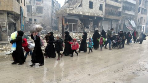 Syrian residents, fleeing violence in the Bustan al-Qasr neighborhood, arrive in Aleppo's Fardos neighborhood on December 13.