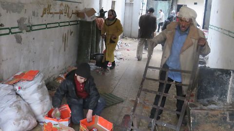 Syrian civilians take food from a storage room that was formerly held by the opposition forces in eastern Aleppo's al-Kalasseh neighborhood on December 13.