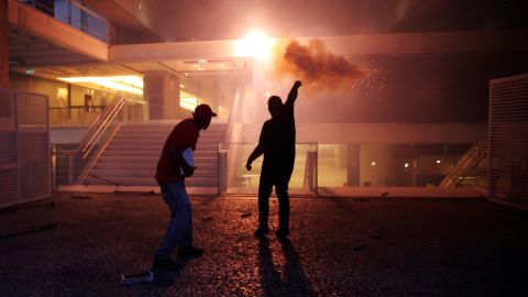 Protesters throw a flare towards the Sao Paulo Industry Federation building in Sao Paolo, Brazil, on Wednesday, December 14. Protests erupted across 15 cities in Brazil as lawmakers voted to pass constitutional amendment PEC 55, which will limit public spending over a 20 year period.