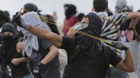 A protester fires a slingshot at police during a demonstration in Brasilia on December 13.