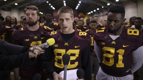 University of Minnesota wide receiver Drew Wolitarsky, flanked by quarterback Mitch Leidner, left, and tight end Duke Anyanwu stands in front of other team members as he reads a statement on behalf of the players in the Nagurski Football Complex in Minneapolis, Minn., Thursday night, Dec. 15, 2016.  The players delivered a defiant rebuke of the university's decision to suspend 10 of their teammates, saying they would not participate in any football activities until the school president and athletic director apologized and revoked the suspensions. If that mea