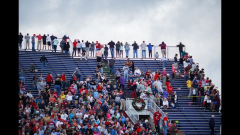 Attendees gather at the top of the stands to peer into the parking lot as Trump's motorcade arrives.