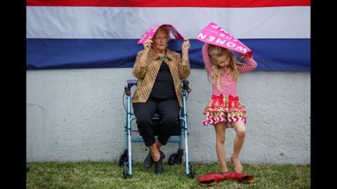 """Mary Nell Moseley and her 8-year-old great granddaughter Lilly Key try to stay dry as they wait for Trump to speak. """"I think he'll be wonderful for women,"""" Moseley said. """"I think he's gonna be good for everybody."""""""