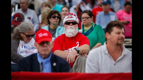 David Docter of Foley, Alabama, sits in the stands wearing a Santa hat and a Trump shirt.