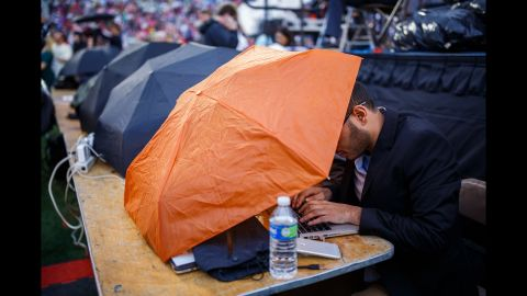 Reporters work in the rain during the rally. There were fewer people at this year's event, perhaps because of the weather.
