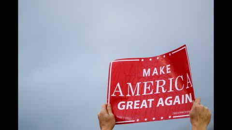 """A Trump supporter holds up a rain-soaked """"Make America Great Again"""" sign."""