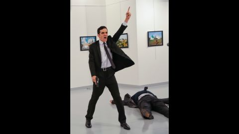 """The gunman gestures near the body of Karlov. In a video circulating on social media, the shooter is heard shouting, """"Allahu akbar (God is greatest). Do not forget Aleppo! Do not forget Syria! Do not forget Aleppo! Do not forget Syria!"""" Russia has been instrumental in helping Syrian President Bashar al-Assad's regime in its push to retake the eastern sector of Aleppo, which had been held by rebels for nearly four years. Russia is also the most powerful ally of Assad's regime and has carried out airstrikes since September 2015 to prop up the embattled leader."""