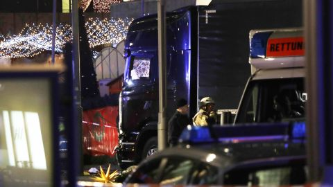 Police stand beside the damaged truck that crashed into the market.