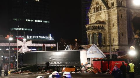 Policemen stand next to a truck that crashed into a Christmas market in Berlin, on December 19, 2016 killing at least one person and injuring at least 50 people. Ambulances and police rushed to the scene after the driver drove up the pavement of the market in a central square popular with tourists less than a week before Christmas, in a scene reminiscent of the deadly truck attack in Nice.