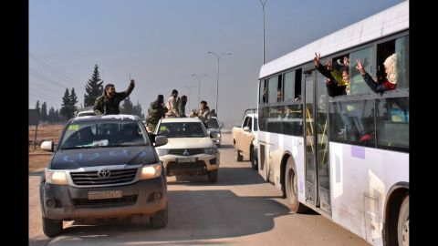 Syrian pro-government forces wave to evacuees from the villages of Foua and Kefraya on December 19. While people were being bused out of Aleppo, safe passage was also given to people in areas held or besieged by rebels, the Aleppo Media Center activist group said.