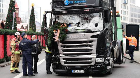"""A policeman and firemen stand next to a truck on December 20, 2016 at the scene where it crashed into a Christmas market near the Kaiser-Wilhelm-Gedaechtniskirche (Kaiser Wilhelm Memorial Church) in Berlin. German police said they were treating as """"a probable terrorist attack"""" the killing of 12 people when the speeding lorry cut a bloody swath through the packed Berlin Christmas market."""