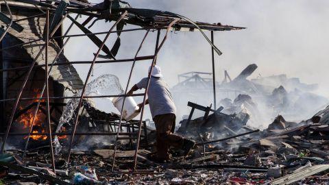 A man throws water over burning debris.