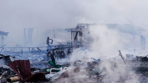 A man works to extinguish the smoldering remains of the market.