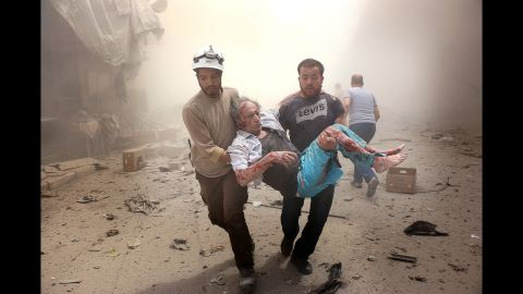 Search and rescue team members carry an injured man after Syrian regime airstrikes targeted the Meshed neighborhood of Aleppo on July 21, 2016.