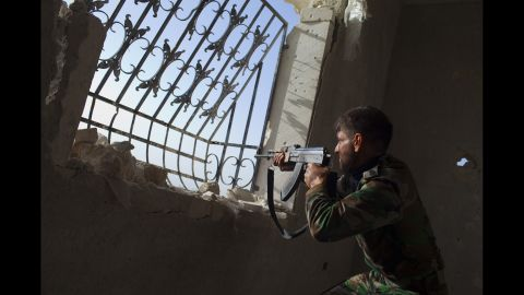 A rebel fighter aims his weapon toward Syrian government forces' positions at the Menagh military airport near Aleppo on March 13, 2013.
