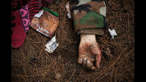 The body of a Syrian army soldier lies on the ground after heavy clashes with government forces at a military academy besieged by the rebels in Tal Sheer village, north of Aleppo, on December 16, 2012.