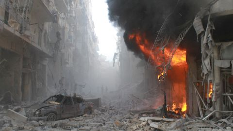 Debris covers a street and flames rise from a building after a reported airstrike by Syrian government forces on March 7, 2014, during the Friday prayer in the Sukkari neighborhood of  Aleppo.