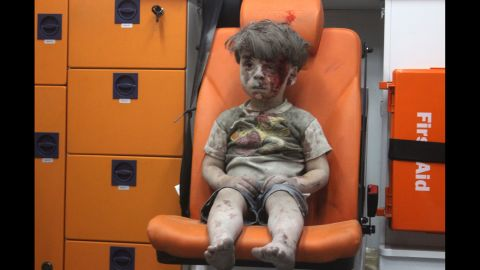 """Wounded 5-year-old <a href=""""http://www.cnn.com/2016/08/17/world/syria-little-boy-airstrike-victim/"""" target=""""_blank"""">Omran Daqneesh</a> sits alone in the back of an ambulance after he was injured during a Russian or Assad regime forces airstrike targeting the Qaterji neighborhood of Aleppo on August 17, 2016."""