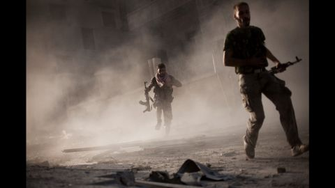 On September 7, 2012, Free Syrian Army fighters run after attacking a Syrian army tank during fighting in the Izaa district of Aleppo.