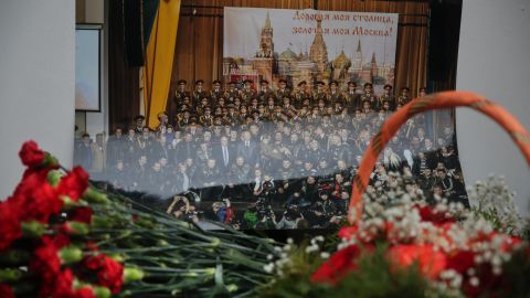 """Flowers lay in front of a photo of the Alexandrov Ensemble at the group's building in Moscow. """"These people always performed in war zones, they wore uniforms, they brought kindness and light,"""" Kibovsky said."""