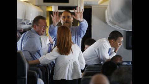 Obama talks on the phone aboard his plane as members of the campaign travel to St. Paul, Minnesota, in June 2008.